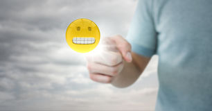 Man in tshirt pointing at emoji with flare against cloudy sky Royalty Free Stock Photos