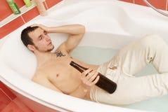 Man in the tub wearing underpants. Drunken man in the tub wearing underpants with a bottle stock image