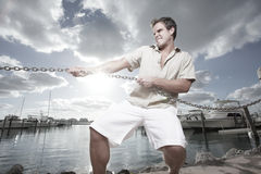 Man tugging on a chain. Young man tugging on a chain with force royalty free stock images