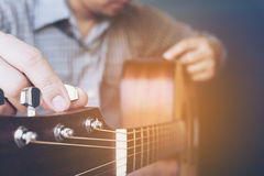 Man tuning acoustic guitar Royalty Free Stock Images