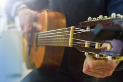 Man tuning acoustic spanish guitar. Play guitar lesson royalty free stock image