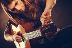 Man is tuning the guitar. Stock Photos
