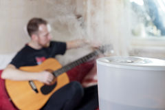 Man tuning his guitar on the background of humidifier Stock Photos