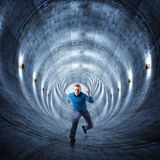 Man in tunnel. 3d image of concrete tunnel and running man Royalty Free Stock Photo