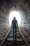 Man in a tunnel looking towards the light. Man silhouetted in a tunnel standing in the center of the railway tracks. looking towards the light at the end of the Royalty Free Stock Photography