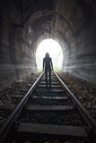 Man in a tunnel looking towards the light Stock Photography