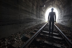 Man in a tunnel looking towards the light Stock Image