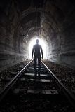 Man in a tunnel looking towards the light. Man silhouetted in a tunnel standing in the center of the railway tracks. Looking towards the light at the end of the Stock Photos
