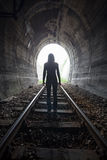 Man in a tunnel looking towards the light. Man silhouetted in a tunnel. Standing in the center of the railway tracks looking towards the light at the end of the Stock Photography