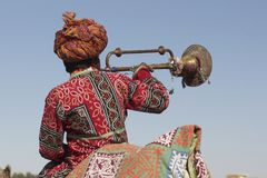 Man in Turban Blowing Trumpet. Man in colorful tunic blowing a trumpet whilst riding a camel in the parade at the start of the Desert Festival, Rajasthan, India Royalty Free Stock Photos