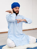 Man in a turban sitting on the mat doing mudra Stock Photos