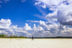 Man in  the turban walking under a cloudy sky. Man in a turban walking on sandy plains under a sky with cumulus clouds on a sunny day Stock Photos