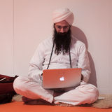 Man with turban working on his notebook at Olis Festival in Milan, Italy Royalty Free Stock Images