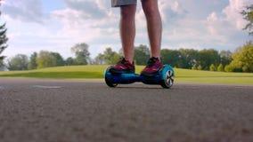 Man turn around on electric self balance board outdoors. Man legs on gyro board. Man turn around on electric self balance board outdoors. Closeup of man legs on stock video footage