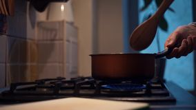 Man turn on gas stove and put on pot to cook dinner at kitchen. Unrecognisable man hand turn on gas stove and put on red pot to cook dinner at kitchen stock video