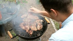 Man turn over large delicious meat steaks, which roast over the coals on barbecue. Grilled food. Meat steak. Man turn over large delicious meat steaks, which stock video footage
