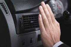 Man turning on air conditioner in car. Closeup Royalty Free Stock Photography