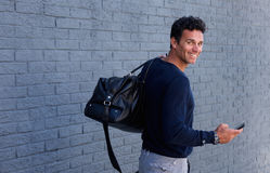 Man turning around smiling with bag and mobile phone Stock Image