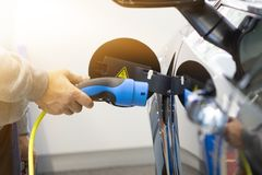 Man turning on charging of car. EV Car or Electric car at charging station. With the power cable supply plugged in on blurred nature with soft light background royalty free stock photography