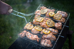 Man is turning cooking grill with chicken. Barbeque. Cooking grill in a hand Royalty Free Stock Images
