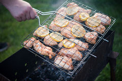 Man is turning cooking grill with chicken. Barbeque. Cooking grill in a hand Stock Image