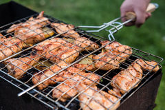 Man is turning cooking grill with chicken. Barbeque. Cooking grill in a hand Royalty Free Stock Image
