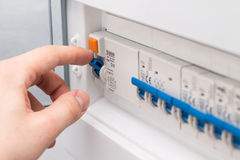 Man turning on the fuse box Royalty Free Stock Photos