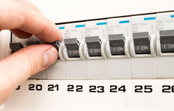 Man turning on the fuse box Stock Photo
