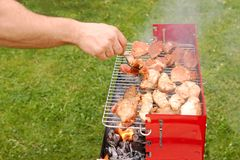 Man turning meat on a barbecue grill Stock Photos