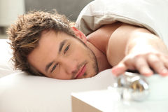 Man turning off alarm clock Royalty Free Stock Image