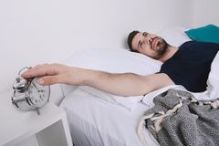 Man turning off alarm clock. Attractive young man turning off the alarm clock. Indoors Royalty Free Stock Images