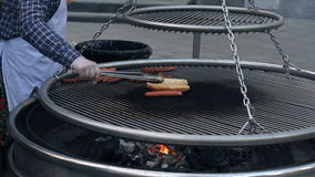 Man Turning The Sausages On The Outdoors Grill. Man In Apron Seen Only By Hands Turning The Sausages On The Outdoors Grill On The Street stock footage