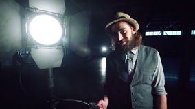 Man turning on studio light. Bearded man in hat and vest standing at studio light stand with switcher in hand, turning it on and checking and smiling, looking at stock footage
