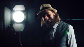 Man turning on studio light. Bearded man in hat and vest standing at studio light stand with switcher in hand, turning it on and checking and smiling, looking at stock video