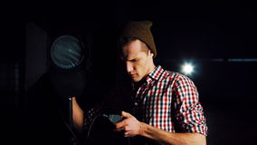 Man turning on studio light. Stylish man in hat and standing at studio light stand with switcher in hand, turning it on and checking and smiling, looking at stock video footage