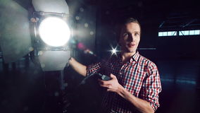 Man turning on studio light. Stylish man in hat and standing at studio light stand with switcher in hand, turning it on and checking and smiling, looking at stock video