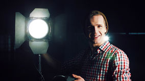 Man turning on studio light. Stylish man in hat and standing at studio light stand with switcher in hand, turning it on and checking and smiling, looking at stock photography