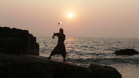 Man turns fire poi standing on a cliff near the ocean at sunset stock video