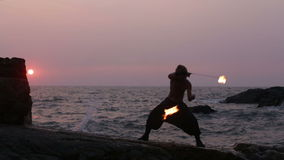 Man turns fire poi standing on a cliff near the ocean at sunset stock footage