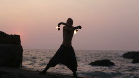 Man turns fire poi standing on a cliff near the ocean at sunset stock video footage