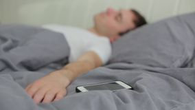 Man turns off the alarm on the phone stock video footage