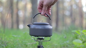 Man turns off gas-stove when kettle is boiling. In forest stock video footage