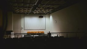 Man turns off the light in the hall. Man turns off the light in the empty conference hall stock video footage