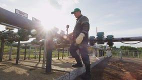 Man Turns Round Valves and Checks Pressure Meters. KAZAN, TATARSTAN/RUSSIA - AUGUST 02 2017: Side view professional employee turns round valves and checks stock video