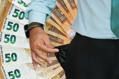 Man turns up his trouser pocket. Background of 50 euro in the background royalty free stock photo