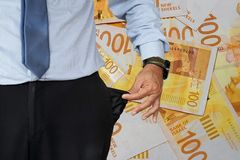 Man turns up his trouser pocket. Background of 100 israeli shekels in the background. stock images