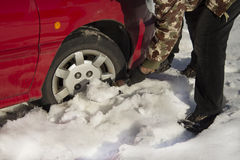 The man turns up shovel wheel of a car with snow drifts. Royalty Free Stock Image