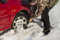 The man turns up shovel wheel of a car with snow drifts. Royalty Free Stock Photo