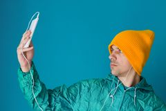 Man in a turquoise sport 90s style jacket and yellow hat holding smartphone with earphones, making selfie ,live broadcast. Young man in a turquoise  sport 90s royalty free stock photo