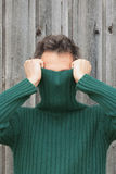 Man with turtleneck covering face. Man pulling turtleneck over his face Royalty Free Stock Photo